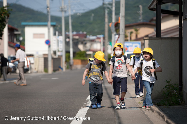 Children walk along a road which had earlier been assessed by a Greenpeace team- led by Jan Beranek - for radioactive contamination, and found to hold high unsafe levels of the contamination, in Fukushima city, in Fukushima prefecture, Japan, on Tuesday 7th June 2011. The city of Fukushima has been contaminated by radioactive fallout from the ongoing crisis at the Fukushima Daiichi nuclear plant. Within Fukushima city the local authorities are now undertaking a clean up of soil from school and nursery school playgrounds.