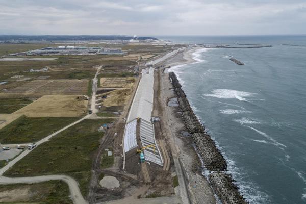 바닷물 유입을 막기 위해 콘크리트 구조물이 태평양 해안을 따라 새로 세워졌다. 멀리 집들이 보이는 마을은 후쿠시마 제1원전에서 북쪽 10km가량 떨어진 나미에 지역이다. 수증기가 나오는 건물은 핵쓰레기 소각공장이다