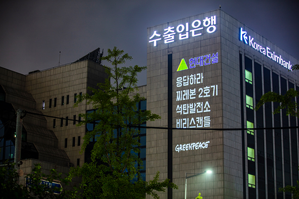 국제환경단체 그린피스 서울사무소가 6월 30일 저녁 여의도 수출입은행 건물에 레이저빔을 투사해 '해외 석탄 투자 멈춰라' 등의 메시지를 새겼다. (출처: 그린피스)