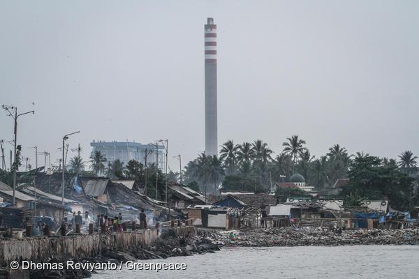 인도네시아 반탄(Banten) 마을 뒤로 석탄화력발전소 굴뚝이 보인다. 이 곳의 주민들은 발전소에서 날아오는 석탄재로 인한 호흡기 및 피부 질환을 앓고 있다.