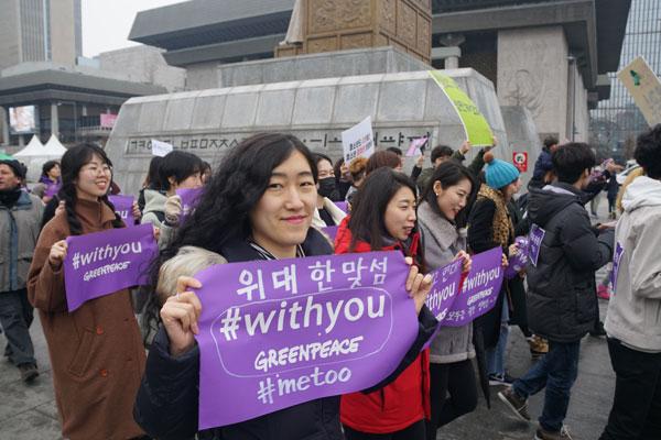 국제환경단체 그린피스 활동가들이 3월 4일(일) 광화문에서 진행된 제34회 한국여성대회에 참여하여, 미투 운동 연대를 의미하는 위드유 동참 현수막을 들고 평화 행진을 하고 있다. 그린피스는 성폭력과 착취, 차별로 인한 피해자들과 연대하고 미투 운동을 지지한다고 선언했다.