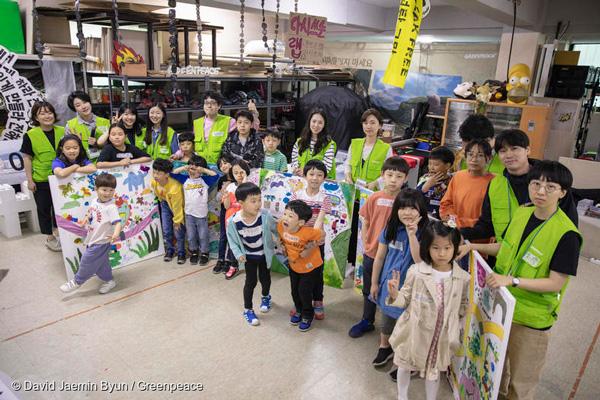 아이들과 그린피스 활동가가 함께 완성한 '미래 교통의 모습' 그림 앞에 서 있다