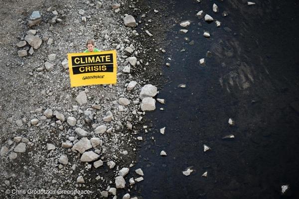 """기후변화의 영향으로 수면이 낮아진 독일 엘베강에서 그린피스 활동가가 """"기후위기(Climate Crisis)""""라고 쓰인 배너를 펼쳐 보이고 있다"""