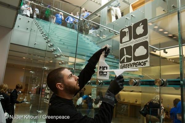 그린피스 활동가가 샌프란시스코 애플스토어에서 재생가능에너지로의 전환을 요구하는 캠페인 스티커를 붙이고 있다