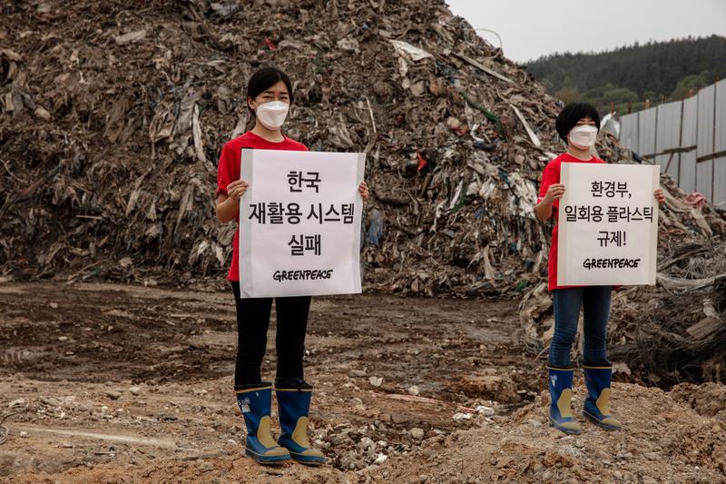 """경상북도 의성의 불법 쓰레기산 앞에서 그린피스 활동가들이 """"한국 재활용 시스템 실패""""라 적힌 현수막을 들고 있다"""