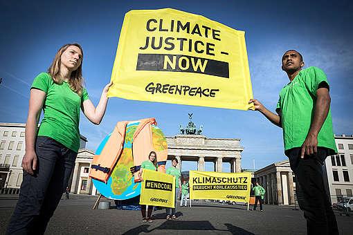 Les militants de Greenpeace présentent un disque de quatre mètres, représentant le monde entier, portant un gilet de sauvetage à la place Pariser à Berlin.