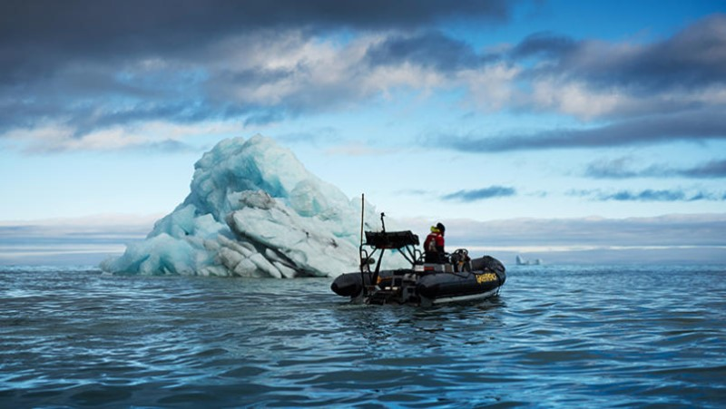 Greenpeace inflatable in front of a blue iceberg in Scoresby Sund fjord, east coast of Greenland.