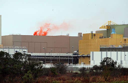 Aktion: rotes Nebelsignal auf dem Dach des Kühlbecken für abgebrannte Brennstoffe im Werk Orano in La Hague