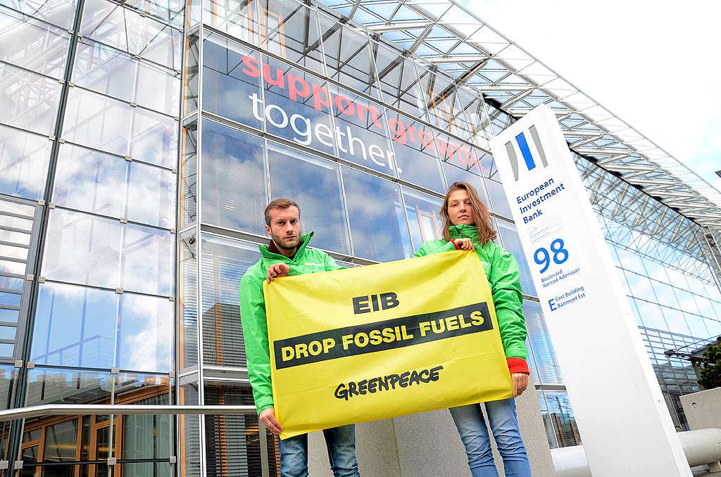 Des activistes devant le bâtiment de la BEI à Luxembourg. Ils tiennent une banderole demandant à la BEI de ne plus investir dans les combustibles fossiles.