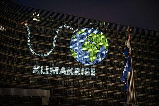 Klimaaktivisten von Greenpeace projizierten eine riesige Animation der Erde als Bombe mit brennender Zündschnur auf das Gebäude der EU-Kommission in Brüssel.