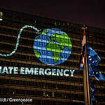 Greenpeace activists in Brussels project an image of the Earth as a bomb with a lit fuse onto European Commission headquarters ahead of an EU summit on EU's top jobs, five-year plan, and response to climate change. The message reads in various languages: Climate Emergency – Time's Running Out – EU Act Now.