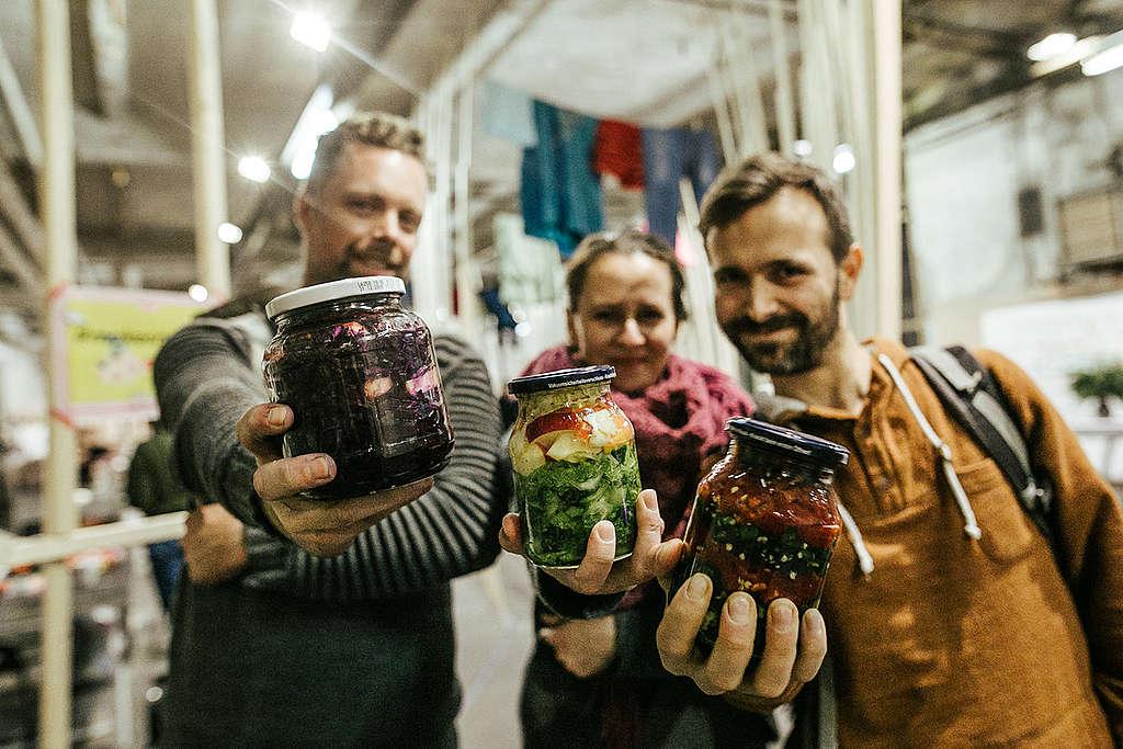 Personas muestran su comida en contenedores reusables © Manuela Clemens / Greenpeace