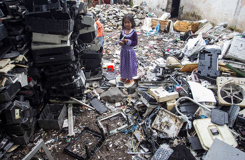 Little Girl plays at Dumpsite for Electronic Waste in Jombang. © Fully Syafi / Greenpeace