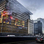 Greenpeace activists wrap the EU summit venue in Brussels with images of giant flames, setting off clouds of smoke, flares and sounding a fire alarm to urge European government leaders to take immediate action to respond to the climate emergency.
