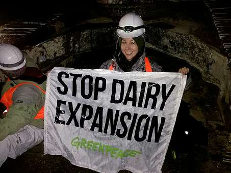 Protestor holds a banner saying 'Stop Dairy Expansion'