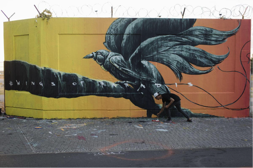 Artist Sokar Uno giving the final touches to his bird of paradise mural in Tempelhof, Berlin.
