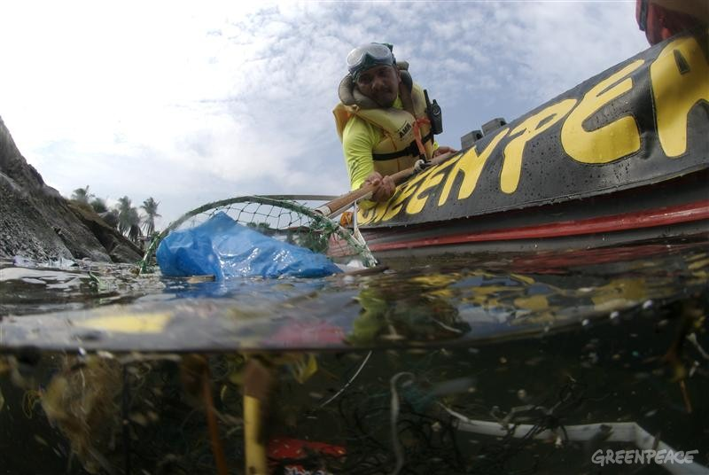 Greenpeace volunteers collect plastic rubbish from Manila Bay. Once a beauty spot it has now become one of the most polluted bodies of water in Asia where sludge, human waste and industrial waste have formed a floating dump.