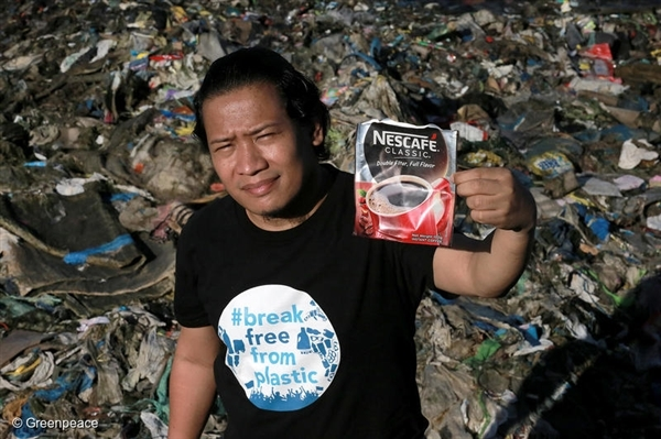 Global Anti Incineration Alliance Philippines Executive Director Froilan Grate shows a discarded pack of a Nestle product as he stands on a trash-filled shoreline along Manila Bay in Navotas City, Philippines.