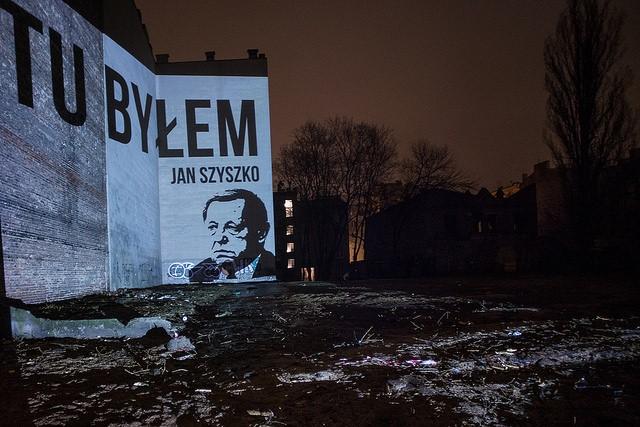 Projekcja napisu Tu byłem Jan Szyszko z portretem ministra na ścianie budynku, obok którego doszło do wycinki na mocy Lex Szyszko