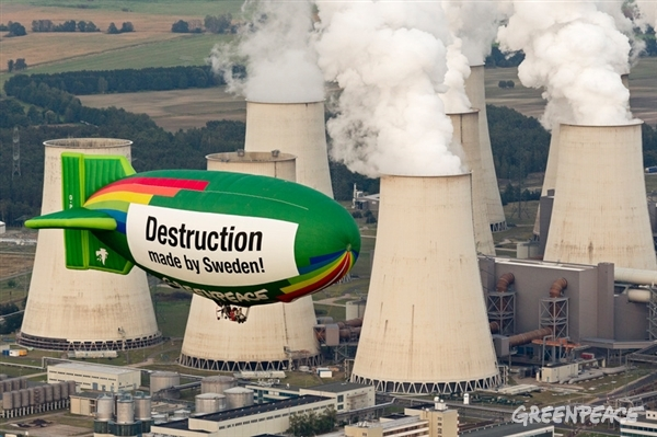 Hot air balloon with message over coal power plant