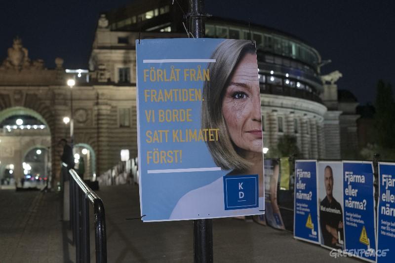 """Greenpeace aktivister sätter upp manipulerade valaffischer föreställande äldre versioner av partiledarna från de 8 riksdagspartierna som ber om ursäkt för att de inte agerat starkare i klimatfrågan när de fortfarande hade en chans. De respektive valaffisherna här ändrats med texten """"Förlåt från framtiden. Vi borde ha satt klimatet först."""" Greenpeace affischeringen genomfördes på natten 7 september, bara några dagar innan valet, i Stockholms innerstad, med fokus på områden kring Riksdagen och är en del av kampanjen """"Klimatet först""""."""