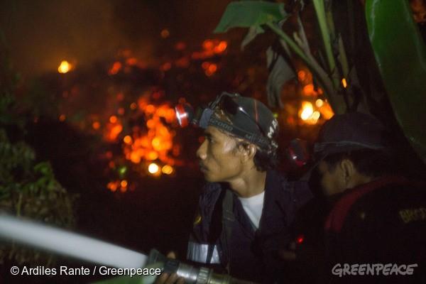 消防員正向泥炭地灌水救火