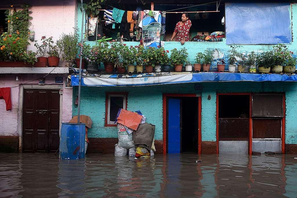 2020年7月20日,尼泊爾加德滿都的季風帶來暴雨,使巴格馬提河水暴漲,一位當地居民站在二樓陽臺目睹淹水的過程。