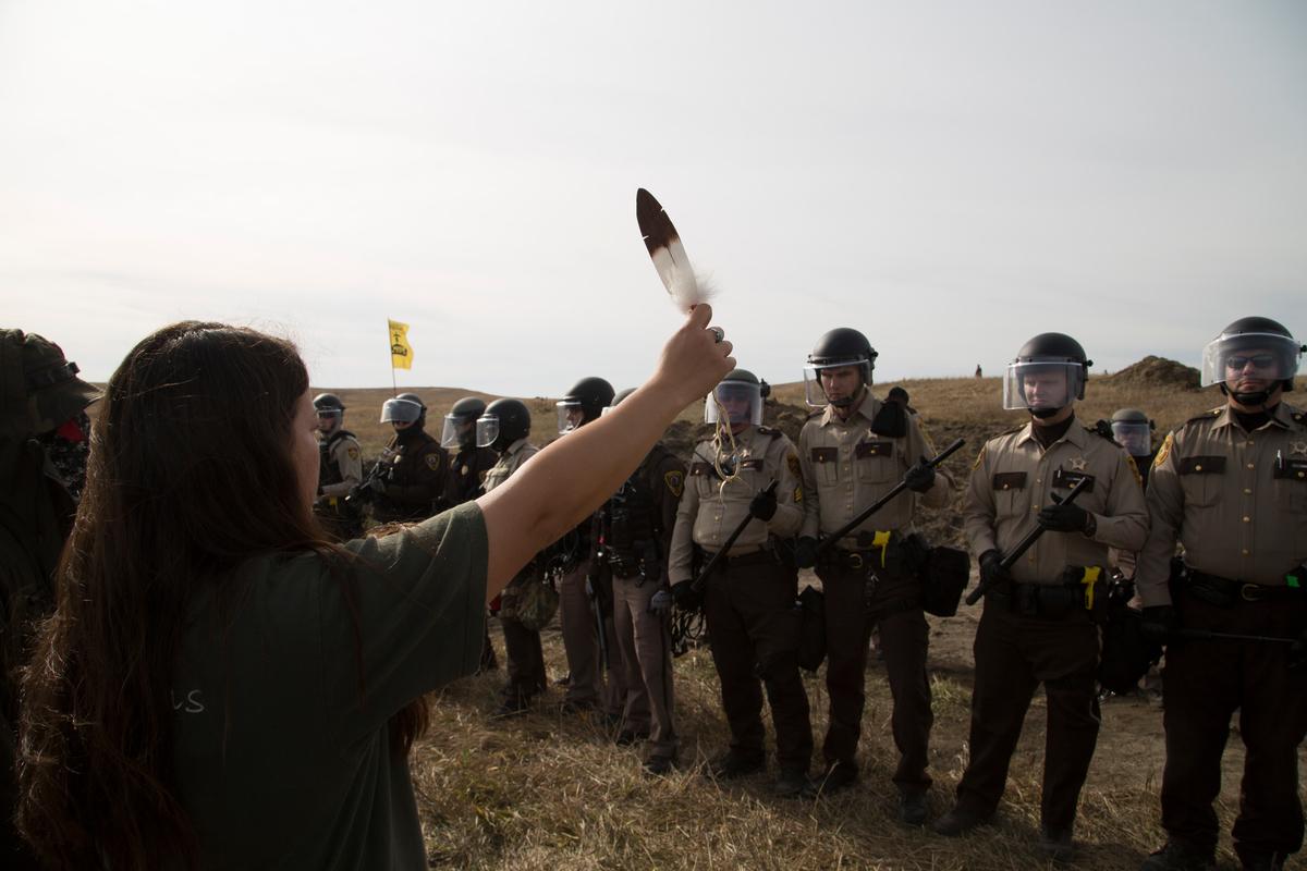 2016年10月,即使面對國家警衛軍及警隊鎮壓,立岩蘇族依然毫無懼色,手持老鷹羽毛以和平行動守護部落家園。