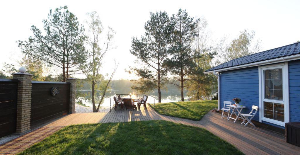Valoisa skandinaavinen piha järven rannalla