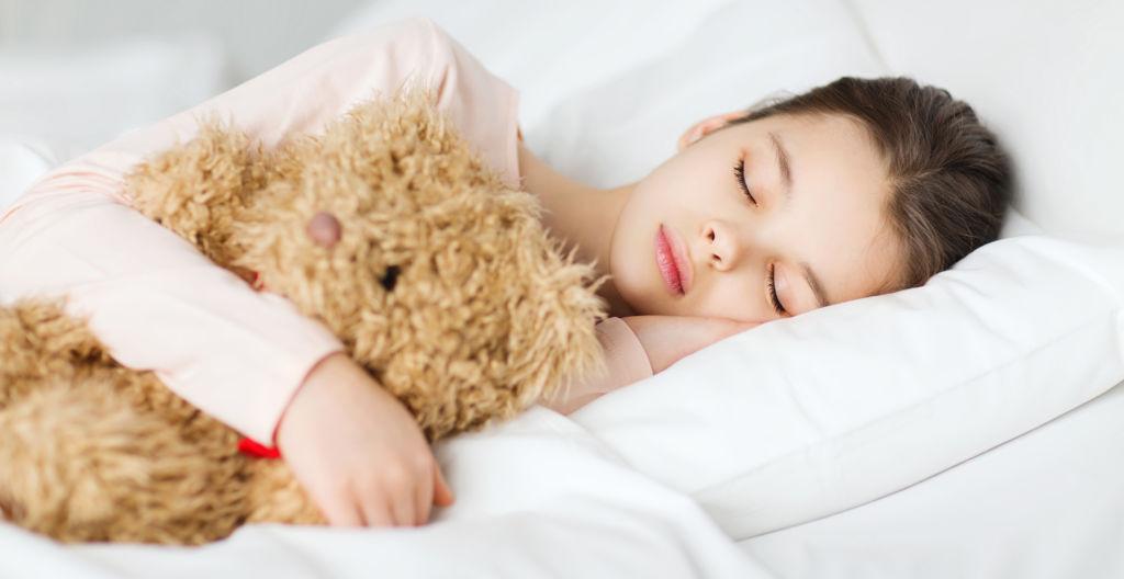 Pieni tyttö nukkuu pehmolelu kainalossaan