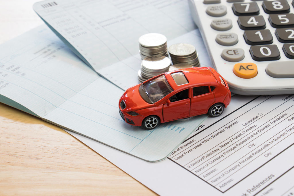Leikkiauto pöydällä rahojen ja laskimen vieressä