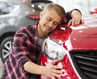 Raitapaitainen mies halaa punaista autoaan