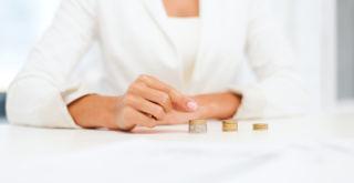 Nainen neljä kolikkopinoa edessään pöydällä.