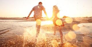 Pariskunta merenrannalla auringon laskiessa
