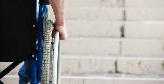 Mies pyörätuolissa portaiden edessä