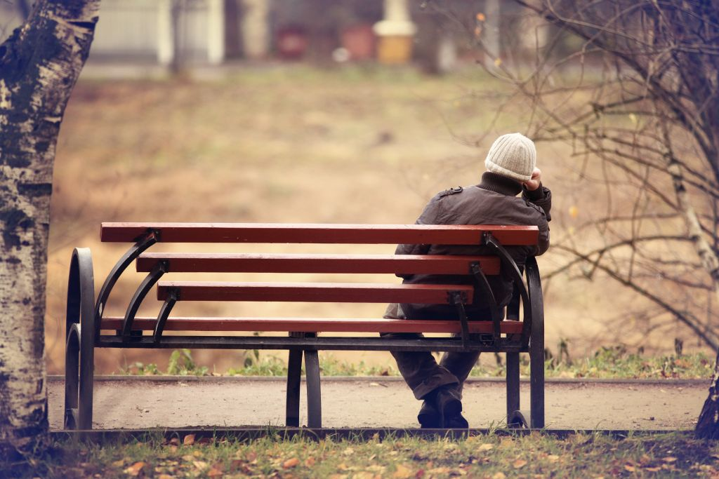 Yksinäinen mies istuu puistonpenkillä