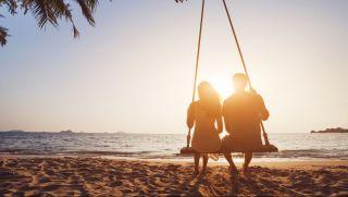 Onnellinen pariskunta rannalla auringon laskiessa