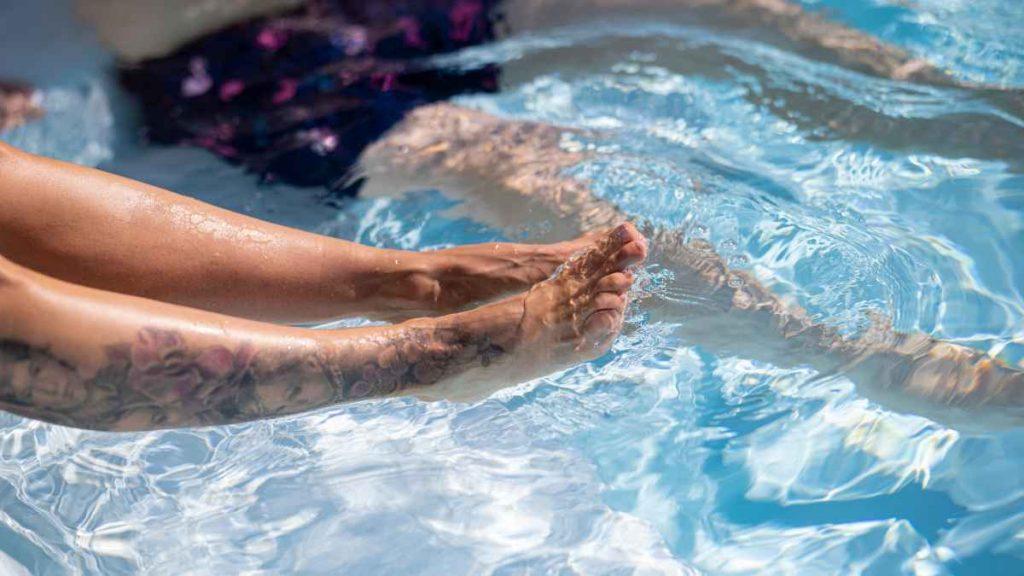 tatuoidut jalat uima-altaassa