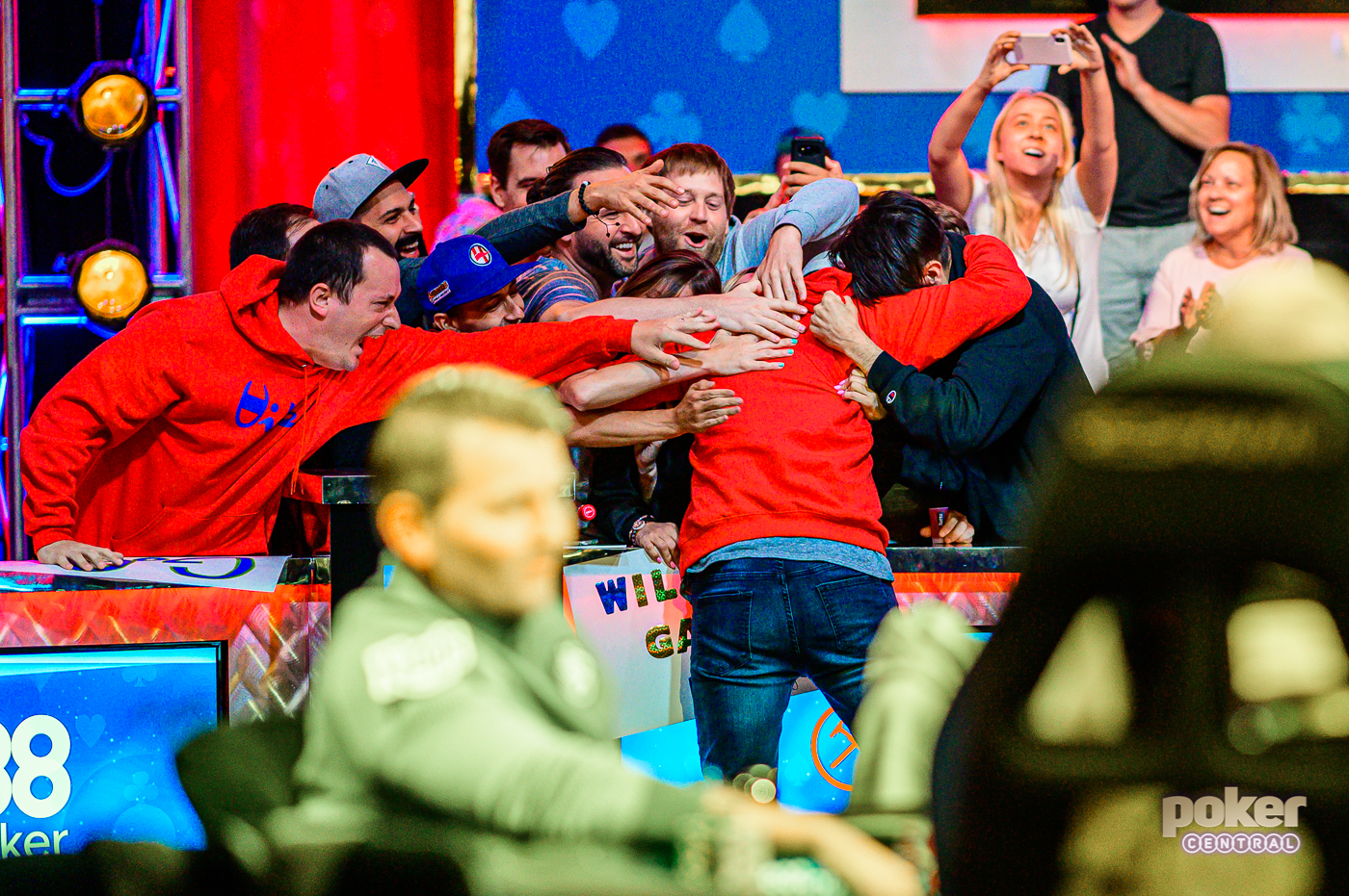 Garry Gates jumps into the arms of his friends and girlfriend celebrating after a big pot.