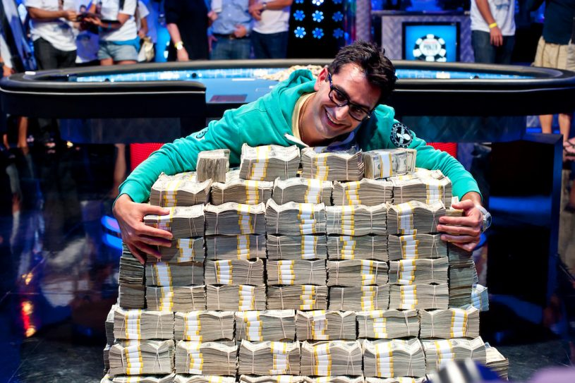 Antonio Esfandiari hugging a stack of $18 million dollars after his Big One for One Drop win in 2012. (Photo: PokerPhotoArchive/Joe Giron)
