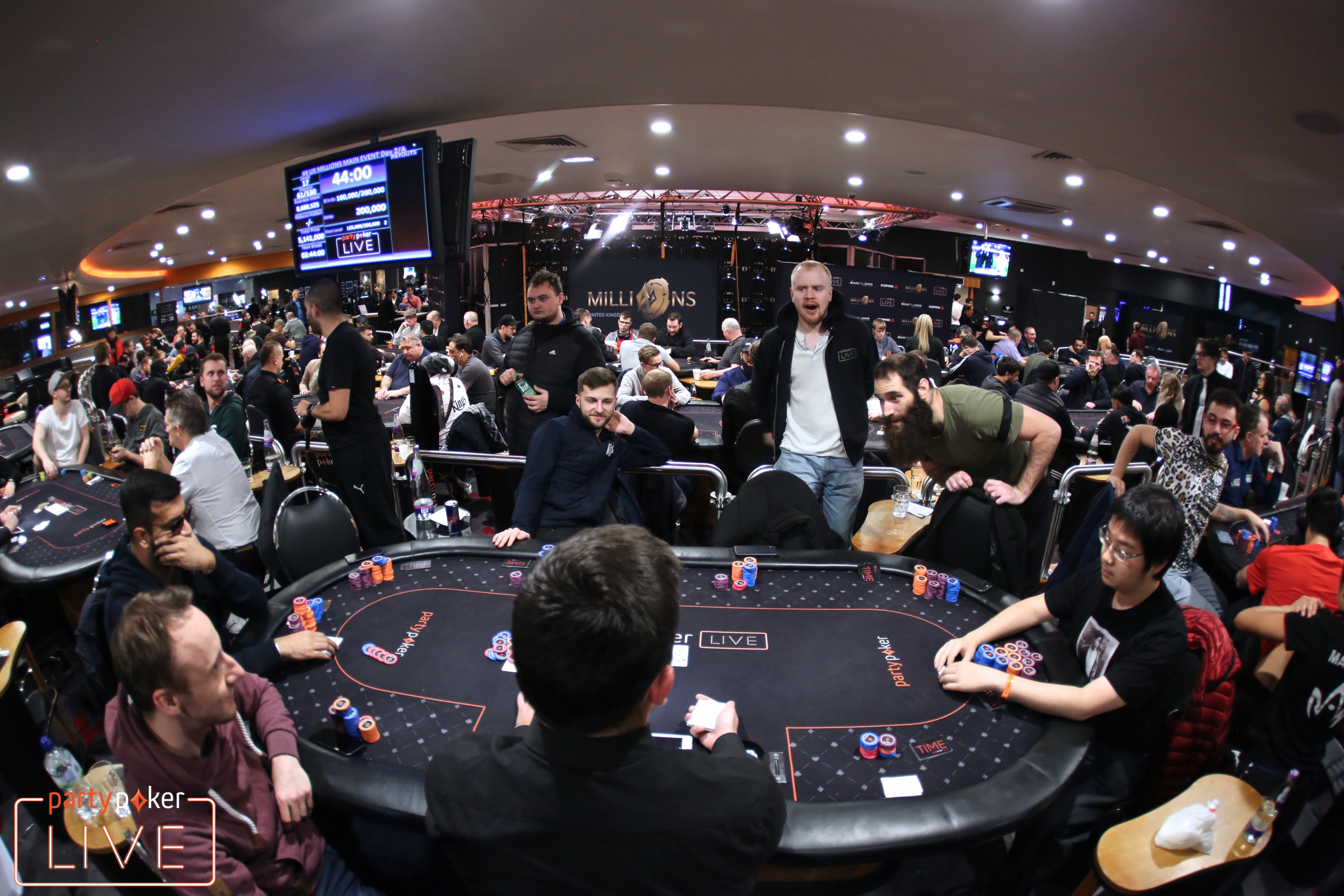 Kuljinder Sidhu (left, seat 2) bubbles the partypoker MILLIONS UK Main Event in a hand against Peter Chien (right, seat 7) (photo: Mickey May/partypoker)