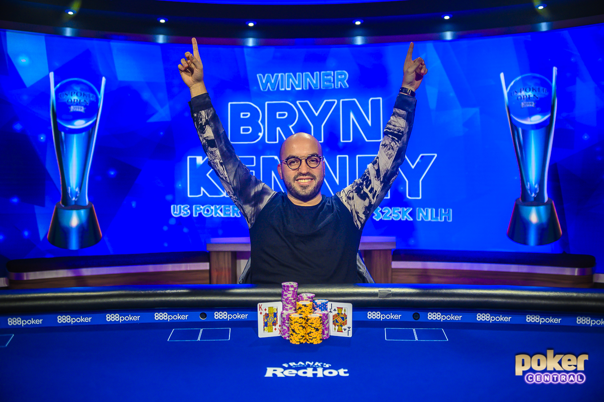 Victorious in U.S. Poker Open Event #7, Bryn Kenney raises his arms aloft.