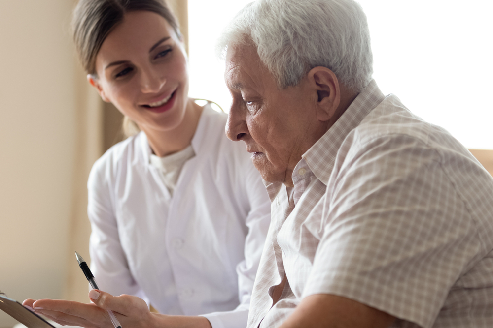 Occupational therapist sits down with senior man to create a treatment plan