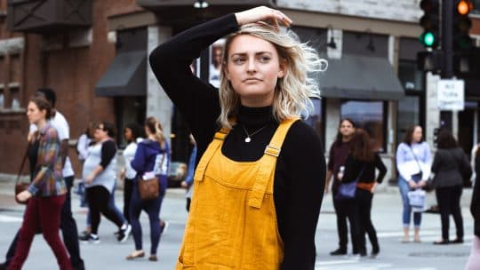 woman in yellow overalls looking confused