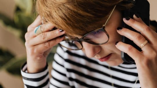 woman worried talking on phone backpayments