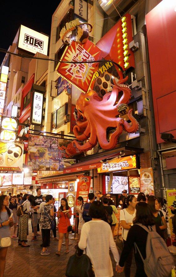 shoppers walking the night market on Dotonbori street in Osaka below a large 3D pink octopus sign