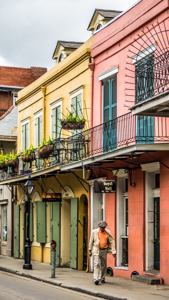 two colorful shop facades, one yellow with green shutters, and one pink with blue shutters, in the French Quarter of New Orleans