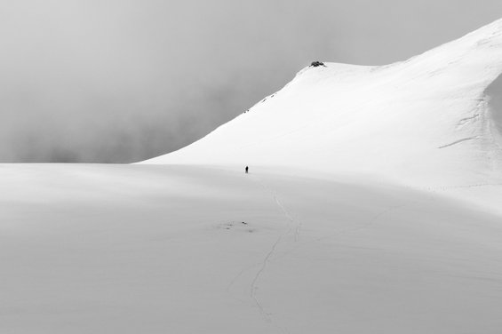 Black and white image of a white sky over a snowy expanse of ground with the minuscule figure of a man in its midst; a hill rises up from the ground to his right.