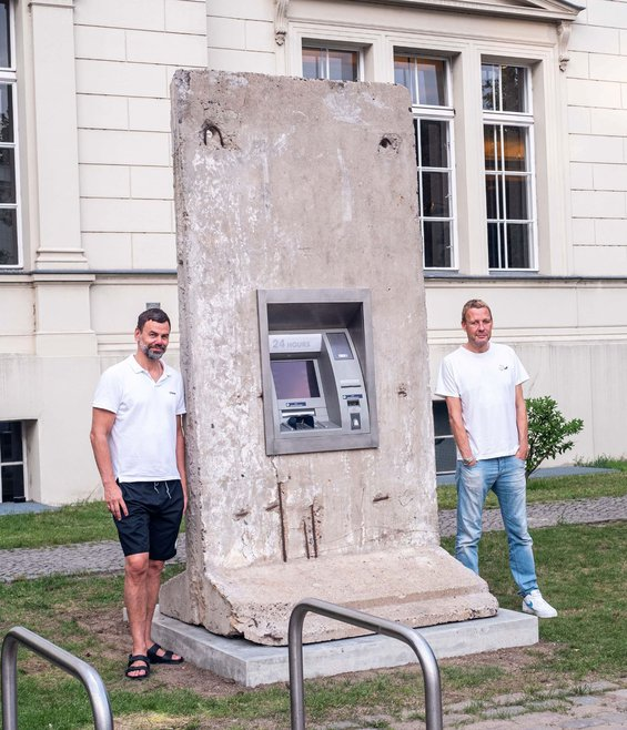 "Elmgreen and Dragset posing on either side of their ""Statue of Liberty,"" a 24-hour ATM set in a rectangular concrete slab."