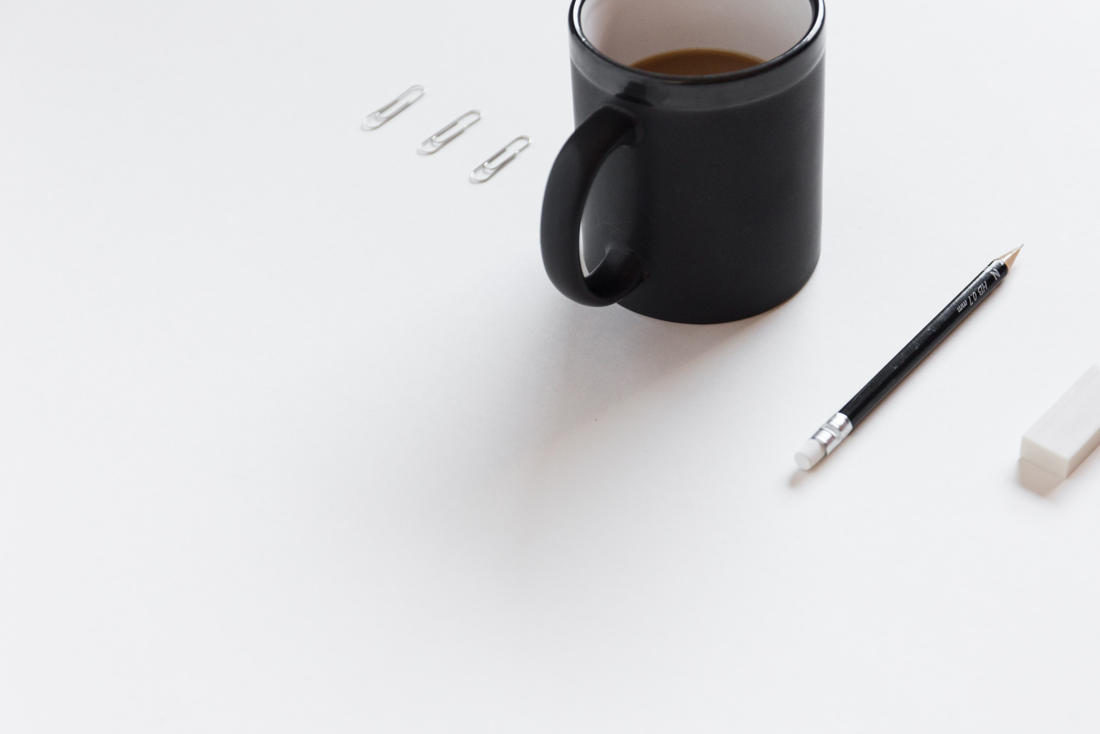 Photo of a desktop with coffee and writing tools
